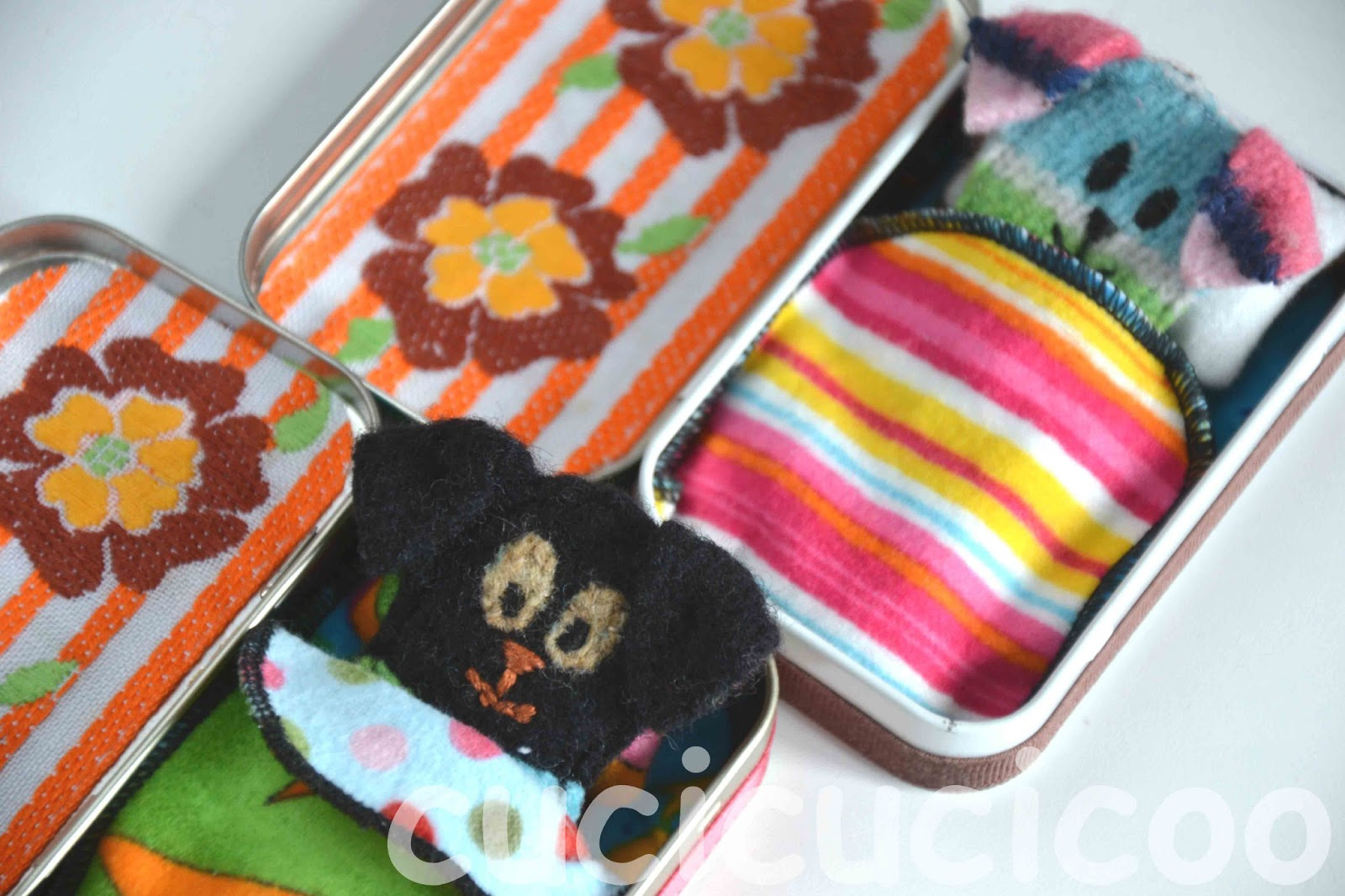 Little toy dogs made from felted wool sweaters in beds from Altoids tins