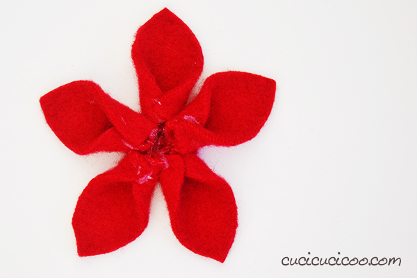 Felt your old wool sweaters in the washing machine and turn them into a no sew felt poinsettia! All it takes are scissors and a glue gun for this easy and festive holiday decoration! #feltedsweaters #diypoinsettia