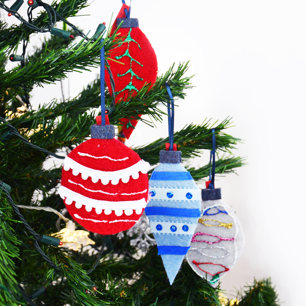 Let your children make their own holiday gifts for others with these easy DIY felt Christmas tree ornaments for kids! Use the free pattern to cut out three shapes from repurposed felted sweaters and decorate! So much fun and eco-friendly! #diychristmasornaments #feltedsweaters