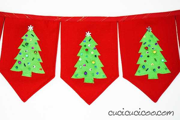 How cute is this?! Decorate your home in handmade holiday style with this DIY Christmas tree banner FREE template and tutorial! Use fabric scraps and beads for customized festive bunting! #christmasbanner #diychristmasbanner #christmastreebanner