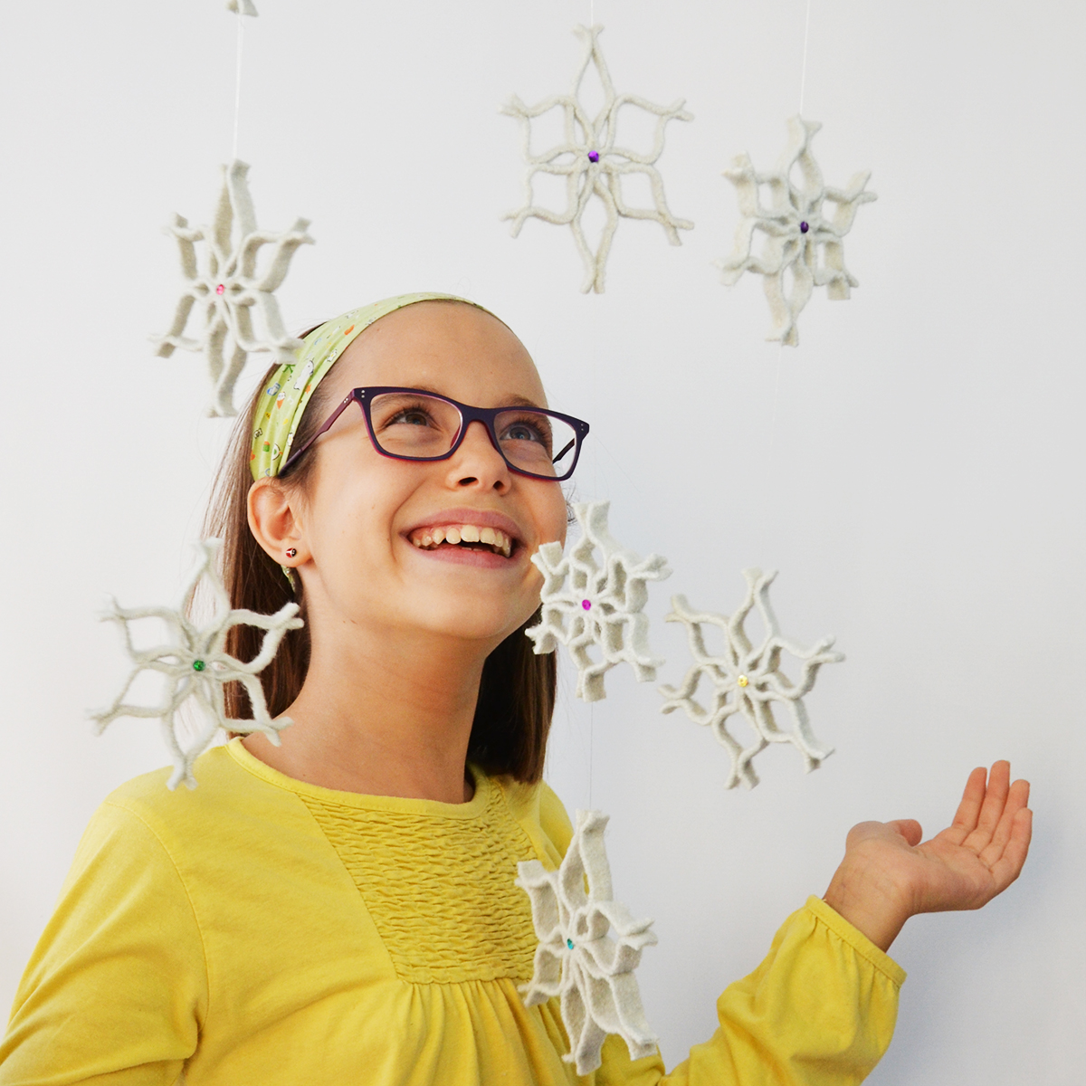 Create the magic of snowfall inside your home, but without the cold! Make these no sew felt snowflake ornaments from a surprising repurposed material: felted wool sweaters! Hang them on the Christmas tree or string them as a garland or from the ceiling for a magical decorative effect! #diysnowflake #feltsnowflake #snowflakechristmasornament