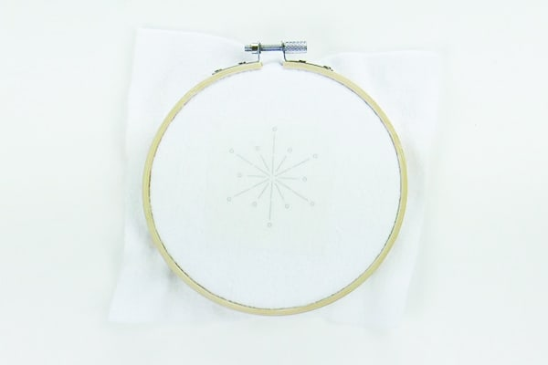 Transfer the snowflake embroidery pattern printed on Stick n Stitch to the fabric in the embroidery hoop.