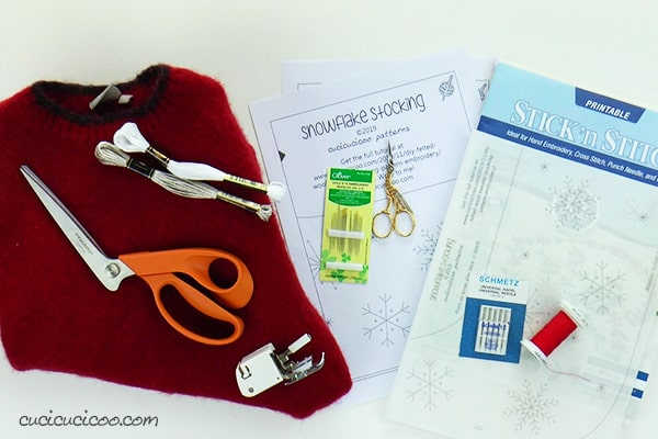 Materials to sew and embroider a Christmas stocking from a felted wool sweater.