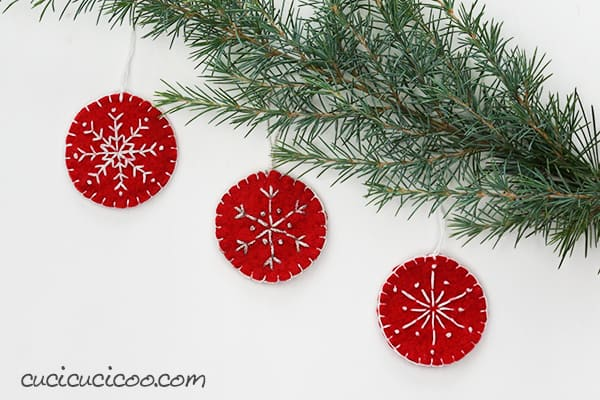 Hand sew these beautiful snowflake embroidered felt Christmas ornaments for your tree or to decorate your home during the holidays. These are easy to create with a free embroidery pattern for three different designs, and require only three basic embroidery stitches. What a perfect handmade Christmas gift! #diyornament #embroideredornament