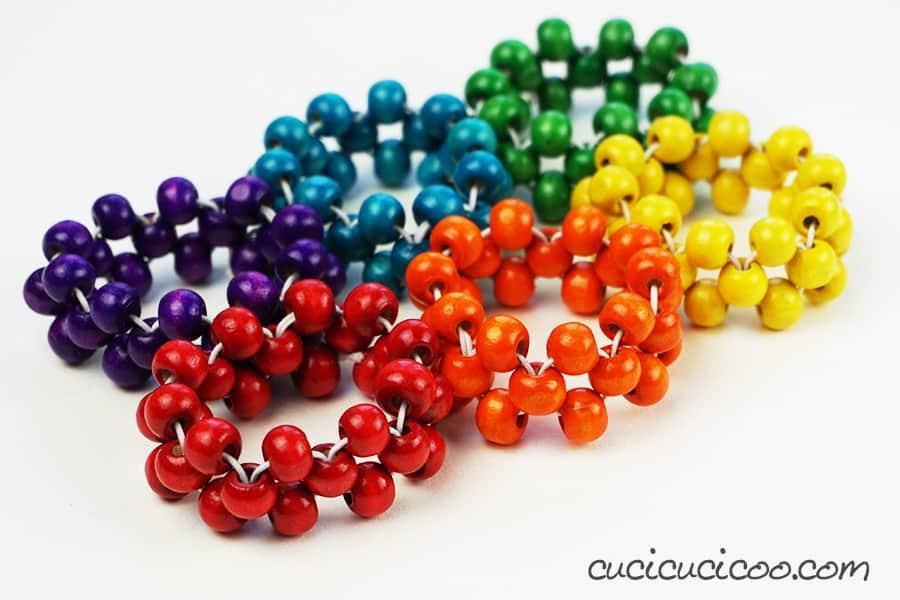 Realizza questi portatovaglioli fai da te con perle di legno ed elastico in tutti i colori dell'arcobaleno per non scambiare più i tovaglioli della famiglia! #portatovaglioli #tovaglioli #perledilegno