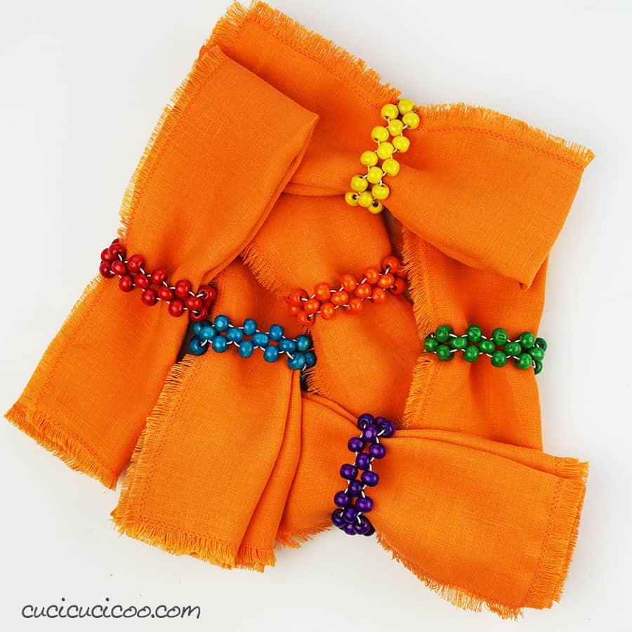 Impara a fare portatovaglioli fai da te con perle di legno e corda di elastic per tenere i tovaglioli di stoffa della famiglia belli e in ordine! Puoi fare un set con vari colori per non confondere i tovaglioli. Ottima idea regalo! #portatovaglioli #tovaglioli #perledilegno