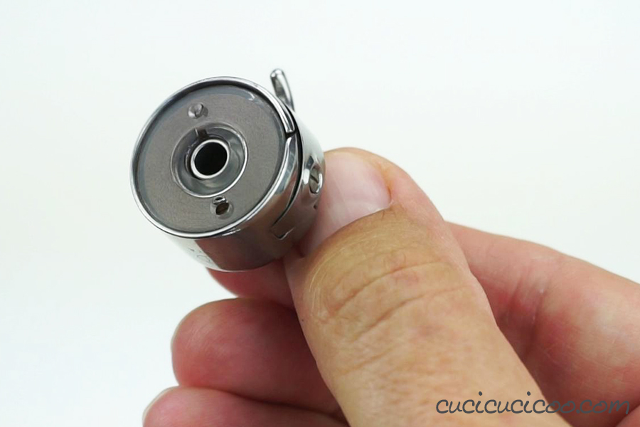La bobina inserita nella scatoletta della bobina per una macchina da cucire a carica frontale.