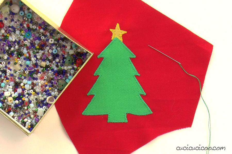Applicare l'albero di Natale alla mascherina natalizia e aggiungere perline per decorarlo. (cartamodello gratis)