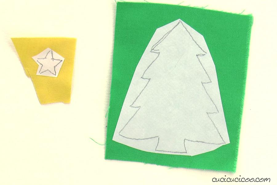 Ritagliare l'albero di Natale e la stella da stoffa per la mascherina natalizia.