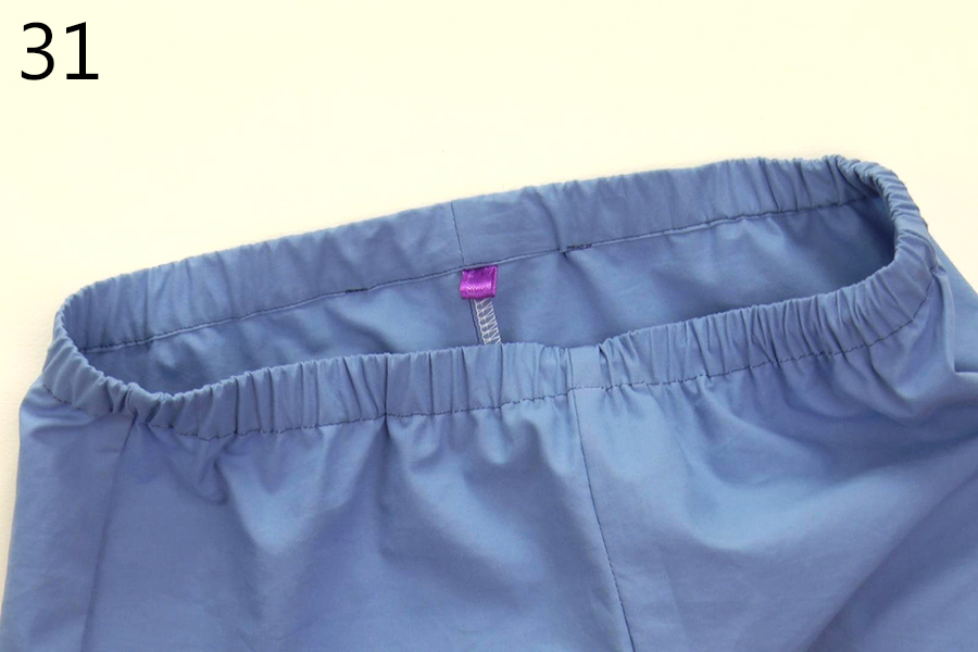 Sew the waistband casing closed at the top of the trousers. A ribbon is inserted as a back tag.