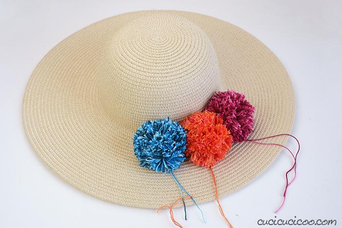 Crea pompon colorati per abbellire un cappello di paglia
