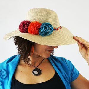 Make your summer hat as unique as you! Learn how to decorate a straw hat with colorful yarn pompoms!