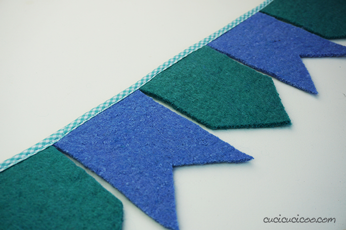 Sew down the bias tape to make gorgeous DIY felt bunting from upcycled sweaters