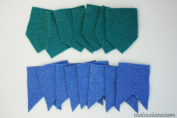 Pieces of an upcycled felted wool sweater cut out to be sewn in a DIY felt bunting.